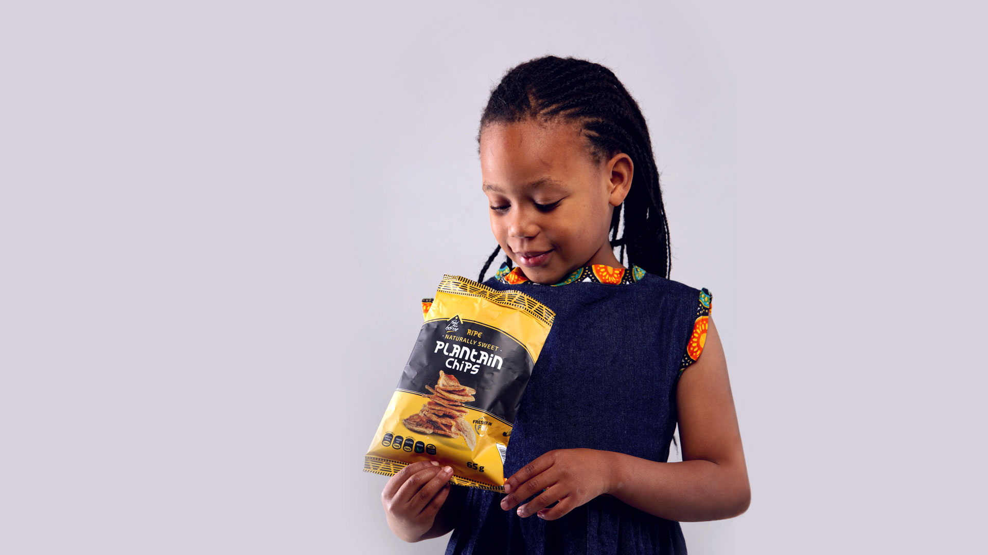 Girl looking at packet of Plantain Chips